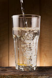 Water pour on to glass on wood table Royalty Free Stock Image