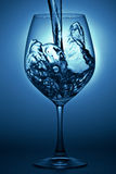 Water pour into wineglass. A water splash stop action shot with blue background stock images