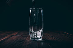 Water poured into an empty faceted glass on a black background. Dark contrast lighting Stock Image