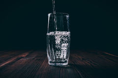 Water poured into a faceted glass on a black background. Dark contrast lighting Stock Images