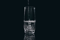 Water is poured into a glass on a black background. Close-up Stock Photos