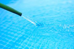 Water is poured from the hose into the pool Royalty Free Stock Photography