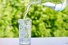 Water is poured from a jug into a glass Royalty Free Stock Photos