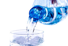 Water poured from a plastic bottle into a glass Royalty Free Stock Photo