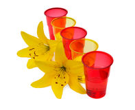 Water is poured into plastic colored glasses. On a white background Stock Image