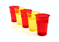 Water is poured into plastic glasses. Water is poured into plastic colored glasses Stock Photos