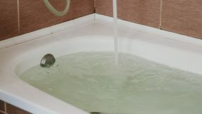 Water poured into the tub. Full bath. Close up. A strong stream of water. Water poured into the tub. Full bath. Close up. A strong stream of water stock footage