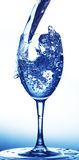 Water poured into wineglass Stock Images