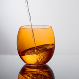 Water pouring into beautiful orange colour glass. Drink. Royalty Free Stock Images