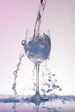 Water pouring into a big size wineglass with many splashes. Stock Photos