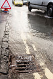 Water Pouring Down Drain On Flooded Road Royalty Free Stock Image