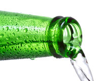 Water is pouring down from green bottle Stock Photos