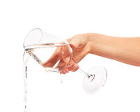 Water pouring from full wine glass in woman's hand Stock Photo