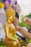 Water pouring and Gilded Buddha statue in Songkran festival trad Royalty Free Stock Photo