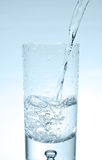 Water pouring into glass. Water pouring into high glass, bubbles in glass Royalty Free Stock Images