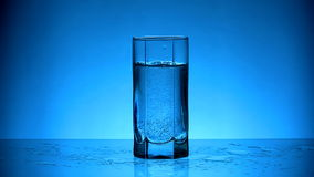Water. Pouring water into glass on blue background