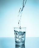 Water pouring into a glass. With blue background Royalty Free Stock Photos