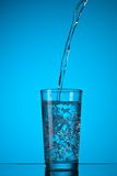 Water pouring into glass on blue Stock Images