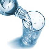 Water pouring into glass from bottle Stock Images