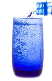 Water is pouring into a glass from bottle Royalty Free Stock Photography