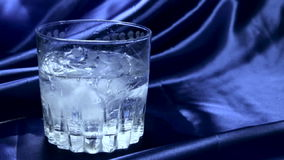 Water pouring into a glass with ice slow motion stock video footage