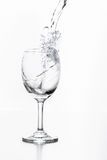 Water pouring in glass isolated. On white Royalty Free Stock Photos
