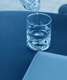 Water Pouring Into a Glass and Laptop Royalty Free Stock Images