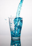 Blue water pouring into a glass Royalty Free Stock Photography