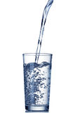 Water pouring into glass on white Royalty Free Stock Images