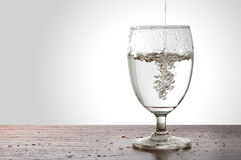 Water pouring into a glass. On wooden table isolated on white background, with clipping path Royalty Free Stock Image