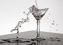 Water pouring into a Martini glass Royalty Free Stock Photography