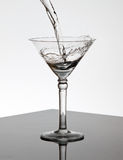 Water pouring into a Martini glass Stock Image