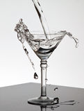 Water pouring into a Martini glass Stock Images