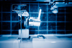 Water pouring from modern faucet in bathroom. Blue tone Royalty Free Stock Image
