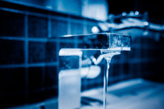 Water pouring from modern faucet in bathroom. Blue tone Stock Images