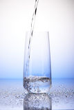Water pouring into one-third full drinking glass on drops Stock Images