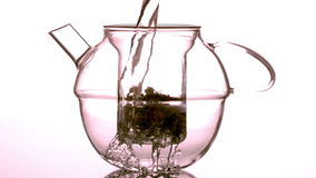 Water pouring over loose tea in teapot stock video footage