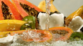 Water pouring over tropical fruit. In slow motion stock video footage