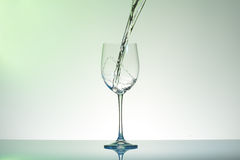 Water pouring into a wineglass creating swirl and splashes. Royalty Free Stock Image