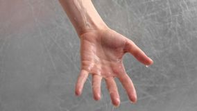 Water is pouring through the woman`s hand. Woman is trying to hold water. Time concept. Hand close-up stock video