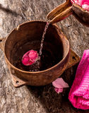 Water Pouring into Wooden Bowl Over Rose Petals Stock Photos