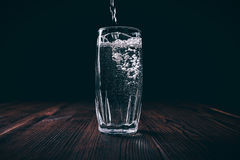Water pours into a full faceted glass on a black background. Dark contrast lighting Stock Photography