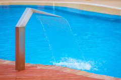 Water pours out of artificial. Waterfall on southern resort pool Stock Photos