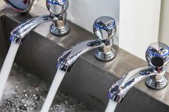 Water pours out of the faucets. Plumbing equipment, fittings, pipes, faucet etc royalty free stock image