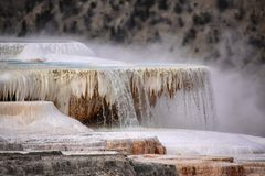 Water pours over a deposited limestone terrace. At Mammoth Hot Springs in Yellowstone National Park, Wyoming Royalty Free Stock Photos