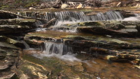 Water pours over the rocks of a creek. View as water pours over the rocks of a creek stock video footage