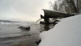 Water pours from the the waste-pipe into the river in winter stock footage