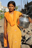Water in Poverty. A poor Indian teenage girl carrying a pot of water on the streetside Royalty Free Stock Photos
