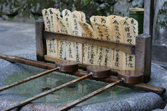 Water and Prayers. A water well with prayers on bamboo in the background. This is at a Japanese temple stock photos