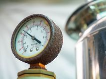 Water pressure gauge  with rust and pipes of a home system royalty free stock photo